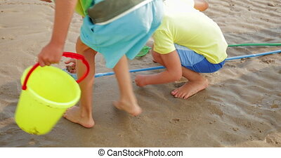 Picking up Shells on the Beach - Two little boys running to...
