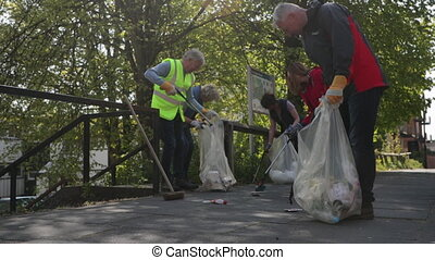 A group of five mature adults picking up litter off the ground outdoors.