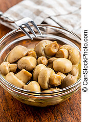Pickled champignons. Marinated mushrooms in glass bowl