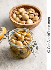 Pickled champignons. Marinated mushrooms in jar.