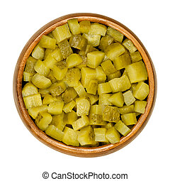 Pickled cucumber, diced, also known as pickle or gherkin, in wooden bowl. Small pickled cucumbers with bumpy skin, cut into cubes. Baby pickles. Close-up from above, over white, isolated food photo.