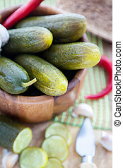 Pickled cucumbers in wooden bowl