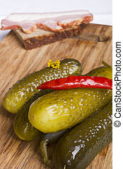 Pickled cucumbers with red hot pepper on a cutting board