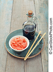 Pickled ginger with soy sauce and wooden chopsticks on plate