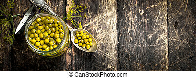 Pickled green peas in glass jar.