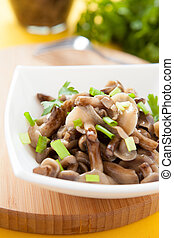pickled honey agarics and green onions in a white bowl