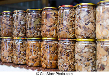 Pickled mushrooms in a glass jar in assortment