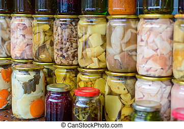 Pickled mushrooms in a glass jar in assortment