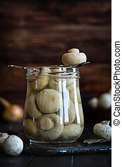 Pickled mushrooms in a glass jar on a dark background. Rustic still life