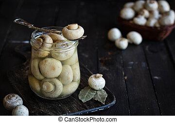 Pickled mushrooms in a glass jar on a dark background. Rustic still life