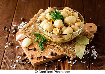 Pickled mushrooms in glass bowl with spices and dill on wooden table.