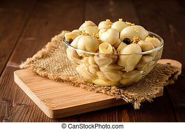 Pickled mushrooms in glass bowl with spices on wooden table.