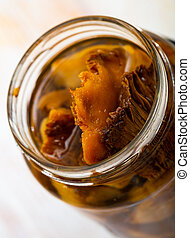 Tasty homemade pickled mushrooms lactarius deliciosus in open jar on table..