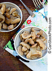 Pickled mushrooms with garlic in white bowl