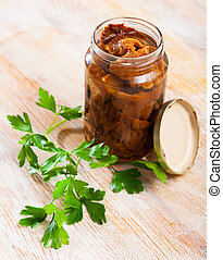 Tasty homemade pickled red pine mushrooms (lactarius deliciosus) in open jar on table with fresh parsley