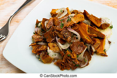 Homemade chopped marinated forest mushrooms lactarius deliciosus with onions on white plate