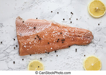 pickled salmon gravlax with pepper and lemon on marble background