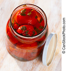 Pickled tomatoes in glass jar