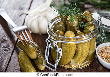 Pickles in a glass on wooden background