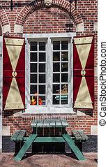 Picknick table under a window with shutters in Harlingen, Netherlands