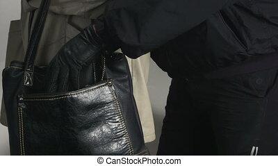 Pickpocket taking wallet from a womans handbag