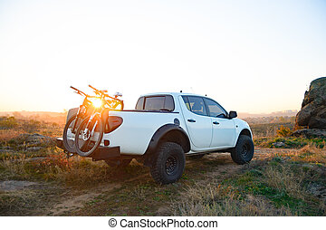 Pickup Offroad Truck with Bikes in the Body in the Mountains at Sunset. Adventure and Car Travel Concept.