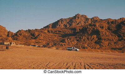 Pickup truck moves Through the Desert in Egypt, on Sand and Mountains Background
