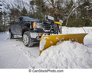 Pickup truck plowing snow during New England winter