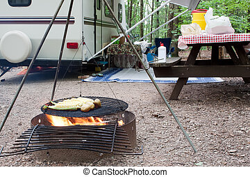 Corn and potatoes on an outdoor grill at a public park with a picnic table and camping trailer in the background.