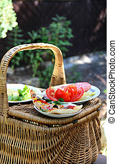 Picnic basket on the green garden background