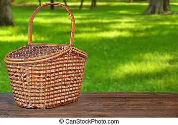 Closed Picnic Basket Or Hamper On The Brown Rustic Wooden Table Or Bench In Park Or Garden Front View, Copy Space