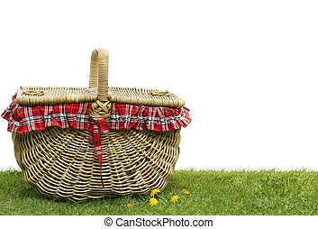 Picnic basket on green grass, over white background. Lots of copy space.