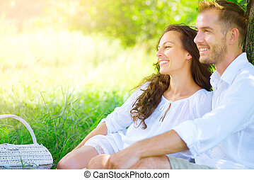 Picnic. Beautiful young couple having romantic dinner outdoors