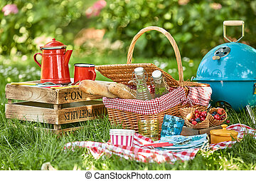 Picnic hamper and BBQ in the shade of a tree