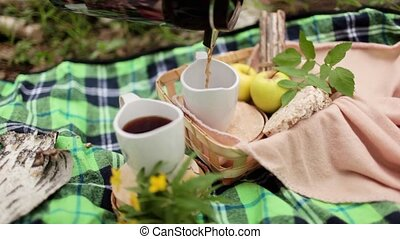 picnic in the forest on fresh air in summer - two mugs of...