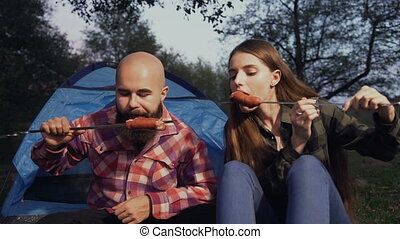 Picnic in the woods. Tourists eat fried grilled sausages