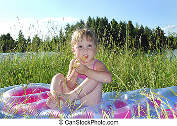 Picnic. Little girl sitting on the grass near the lake