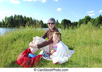 Picnic. Mother with her daughter sitting on the grass near the lake in the summer.