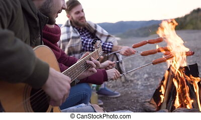 Picnic of young people with bonfire and cooking sausages on the mountains in the evening. Cheerful friends singing songs and playing guitar. Dolly shot