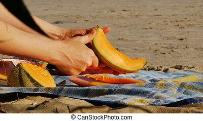 Picnic on a river beach - cutting melon - 4k
