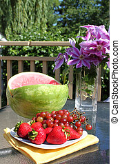 Picnic - Plate of fruit on a table in the outdoors with...