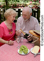 Picnic Seniors - Opening Wine - A retired couple having a ...