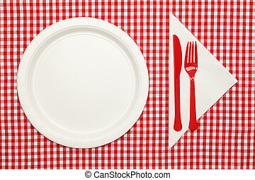 Picnic table setting. Paper plate on red checkered table cloth wtih ...