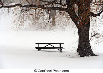 Picnic table in snow under a winter tree