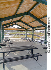 Picnic tables with benches inside a pavilion