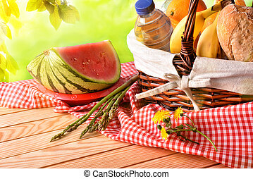 Picnic wicker basket with food on table in field elevated -...