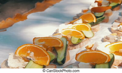 Picnic with butter, pickles, cheese, orange sandwiches arranged on a blanket on the ground.