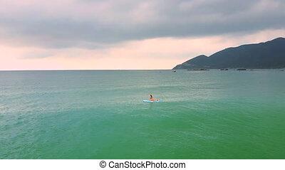 girl figure lies on paddleboard drifting among azure ocean
