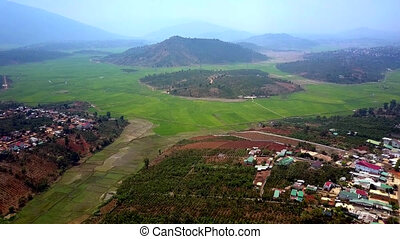 pictorial aerial view from tropical fields to nearby town -...