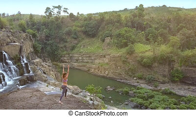 pictorial landscape with waterfall and girl on rock - aerial...